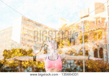 A beautiful athlete stretching her arms against low angle view of city buildings on sunny day