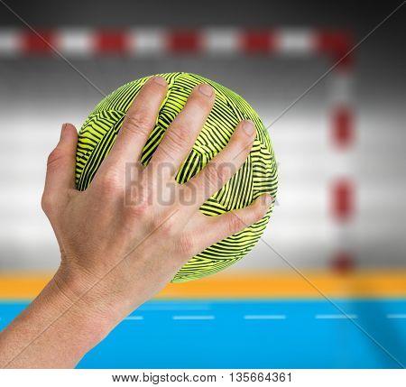 Sportswoman holding a ball against handball field indoor