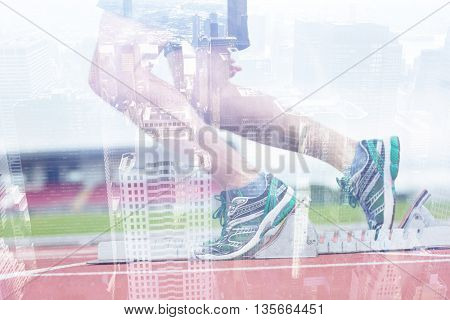 Low section of a man ready to race on running track against image of a city landscape