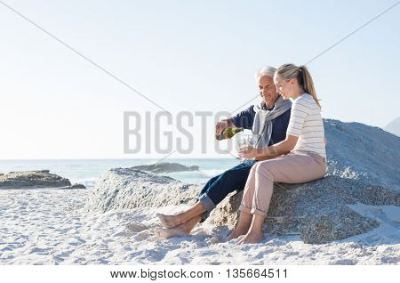 Senior man pouring white wine in glasses for celebrating anniversary with his wife. Happy mature couple sitting on beach while man filling glasses of wine. Smiling couple enjoying white wine at beach.