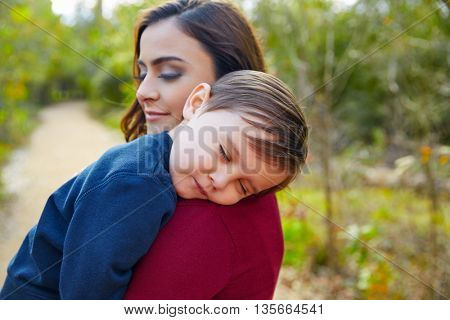 Mother holding kid boy sleeping in her shoulder at park
