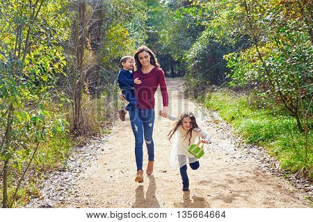 Mother daughter and son family in the park walking in a trail