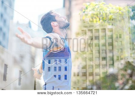 An handsome athlete enjoying the sun against low angle view of city buildings