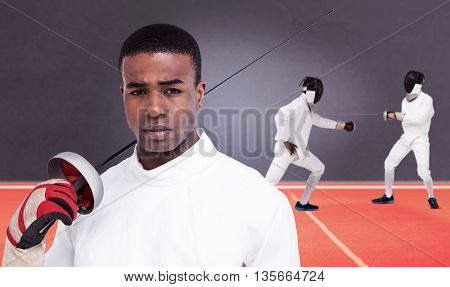 Portrait of swordsman holding sword against digitally generated image of playing field