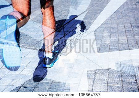 Close up view of athletes legs running against skyscraper