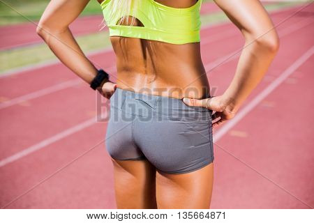 Mid-section of female athlete standing with hand on hip on a running track