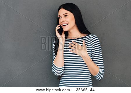 This is unbelievable! Surprised young woman talking on the mobile phone and smiling while standing against grey background