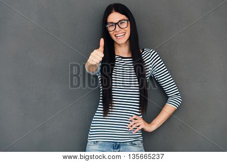Everything is alright! Attractive young woman showing her thumb up and looking at camera with smile while standing against grey background