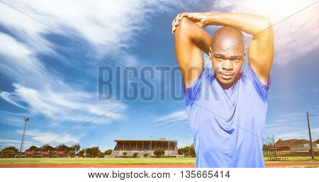Athletic man stretching his arms against view of running track