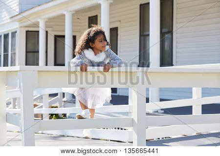 kid toddler girl playing climbing a fence outdoor latin ethnicity