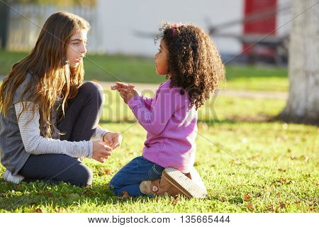 Kid girls playing in a park grass mixed ethnicity outdoors