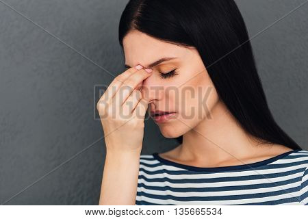 Feeling stressed and tired. Frustrated young woman massaging her nose and keeping eyes closed while standing against grey background