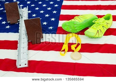 Green trainer shoes, starting block and gold medal on american flag