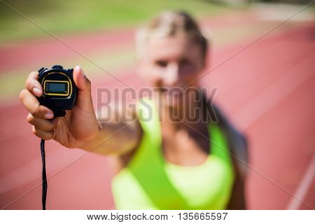 Female athlete showing stop watch on running track