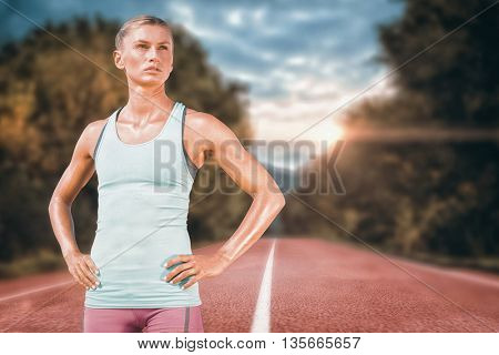Sporty woman posing against running track in the nature