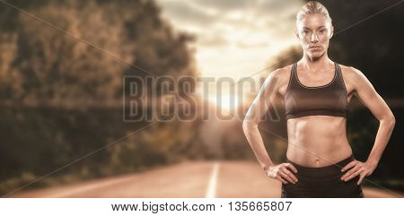 Female athlete standing with hand on hip against running track in the nature