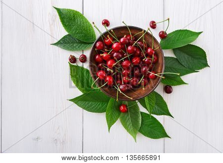 Sweet fresh cherries in a bowl on white rustic wood closeup, fruit backround. Healthy food top view at table