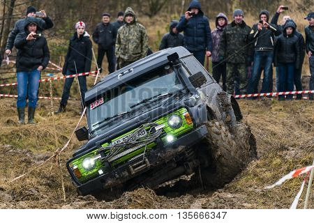 Lviv Ukraine - February 21 2016: Off-road vehicle brand Nissan overcomes the track on a amateur competitions Trial near the city Lviv Ukraine. Audience watching the competitions.
