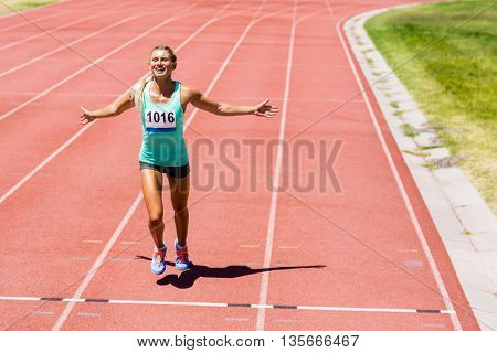 Excited female athlete posing after a victory on racing track