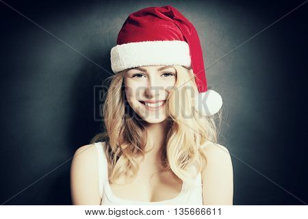 Christmas Woman laugh. Beautiful Xmas Fashion Model in Santa Hat on Blue Background