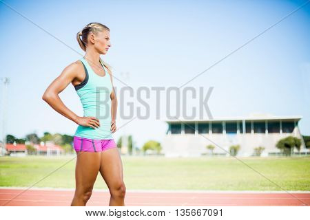 Female athlete standing with hand on hip on running track