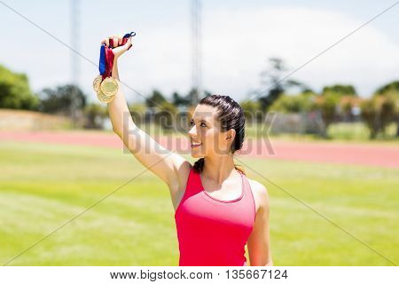 Happy female athlete showing her gold medals in stadium