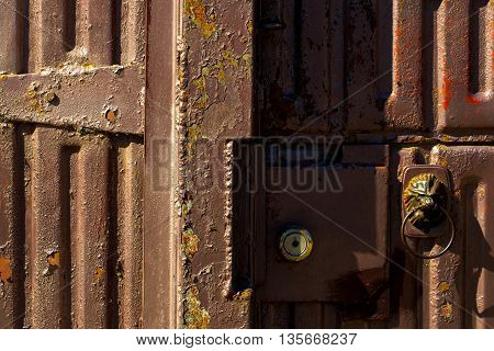 Old iron rusty scratched corrugated door with lock and doorknob with lion image closeup