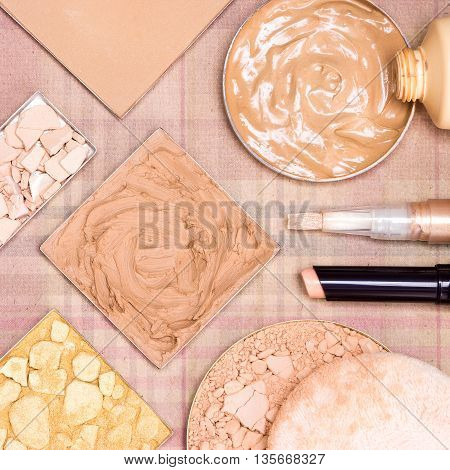 Close-up of makeup products to create beautiful skin tone: concealers, cream-to-powder and liquid foundation, shimmer powder golden color, correcting and compact powder on plaid surface