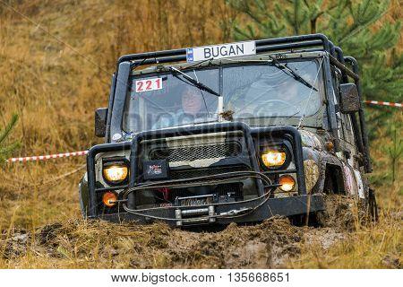 Lviv Ukraine - February 21 2016: Off-road vehicle UAZ (No. 221) overcomes the track on of landfill near the city Lviv.