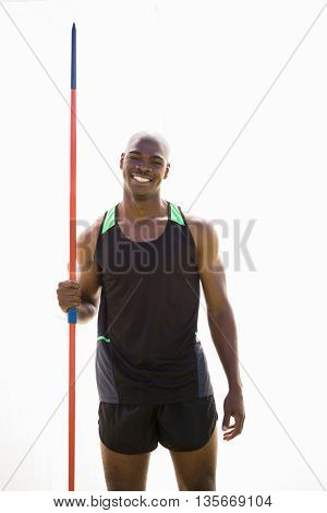 Portrait of happy athlete standing with javelin in stadium