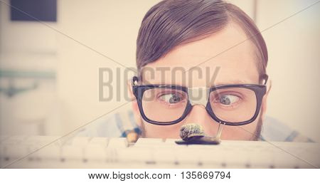 Snail on a white background against nerdy businessman working on computer