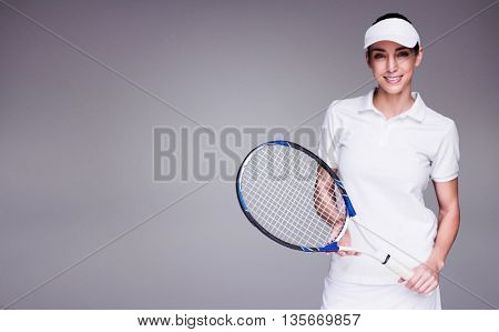 Female athlete posing with tennis racket against grey background