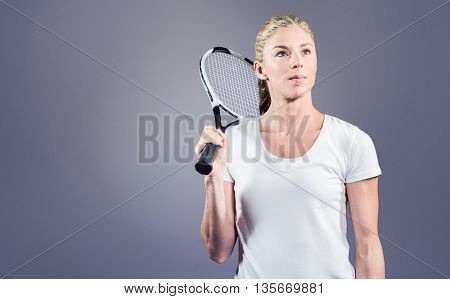 Female tennis player posing with racket against grey vignette