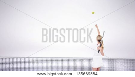 Athlete holding a tennis racquet ready to serve against grey background