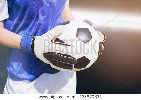 Close up of a football held by sportswoman against spotlight