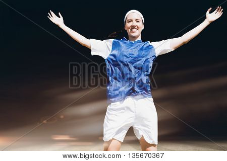 Front view of happy sportswoman raising her arms against football pitch at night