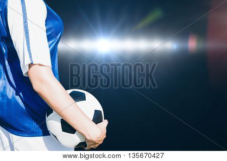 Woman soccer player posing with a ball against spotlight