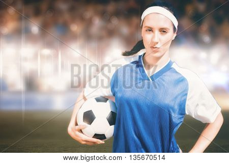 Woman football player posing with football on a white backgorund against sports arena
