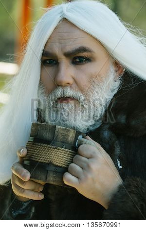 Druid old man with wrinkles long silver beard and hair with wooden mug in hands on blurred background