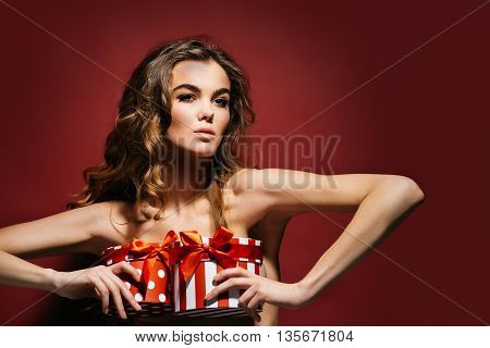 young naked girl with pretty face and bare shoulders has long lush curly hair holding colorful boxes of presents standing on red background copy space