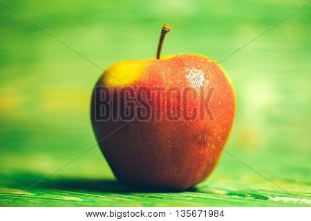 fresh red apple with water drops on bright textured green blurred wooden background
