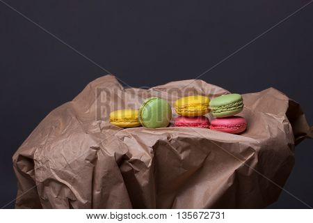 Pink yellow and green macaron on brown paper on grey background copy space