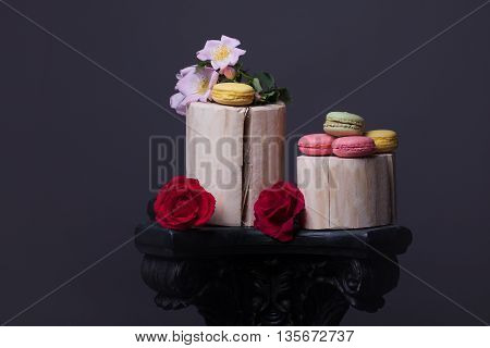 Pink yellow and green macaron on wooden stump with soft spring flowers and roses on grey background copy space