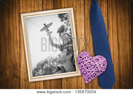 Boy with toy aeroplane sitting on fathers shoulders against wooden background