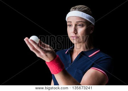 Female athlete playing ping pong on black background
