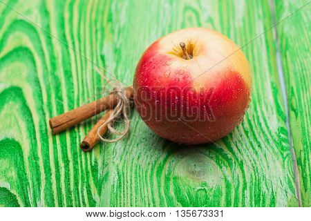 Red Apple And Cinnamon On Green Wood