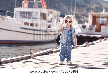 Cute baby girl wearing stylish clothes outdoors. Standing at wooden sea pier. Looking at camera.