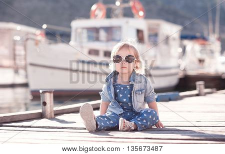 Stylish kid girl wearing trendy denim clothes sitting on wooden sea pier outdoors. Looking at camera. Childhood.