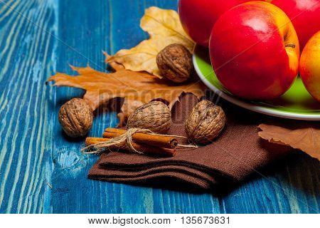 Walnut Apples And Cinnamon On Blue Wood