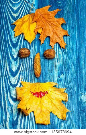 walnuts pinecone and yellow autumn seasonal leaves lying in shape of floral human face smiley on textured blue wooden background